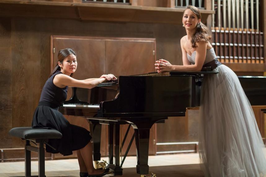画像:声楽家とピアニストがピアノの前で談笑